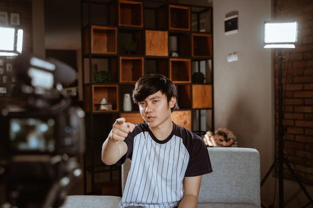 Азиатский vlogger записи молодого человека vlog, говорить с камерой