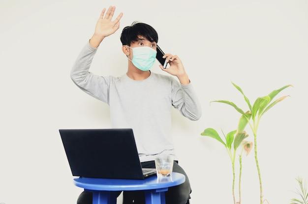彼の仕事で忙しいラップトップの前に座っているマスクを身に着けているアジアの若い男
