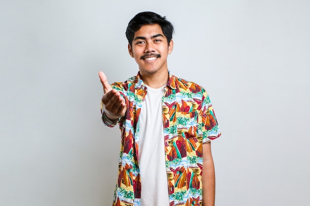 カジュアルな服を着てフレンドリーな笑顔のアジアの若い男は、挨拶として握手を提供し、白い背景の上で歓迎します。成功したビジネス。