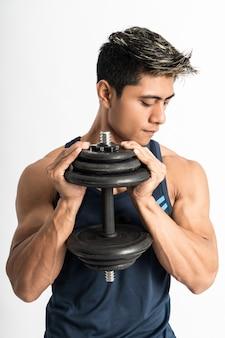 Азиатский молодой человек в спортивной одежде поднимает гантели обеими руками