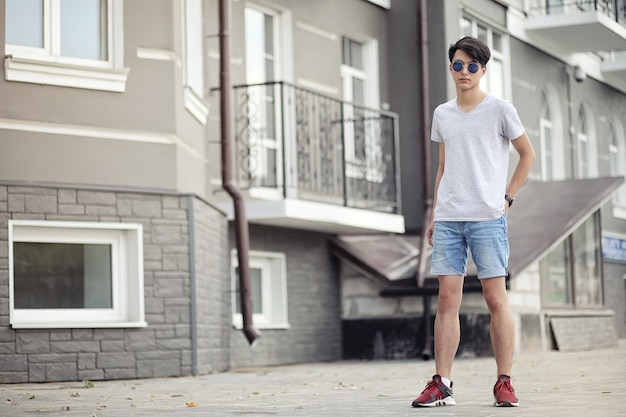 Asian young man wearing sunglasses outdoors in the city