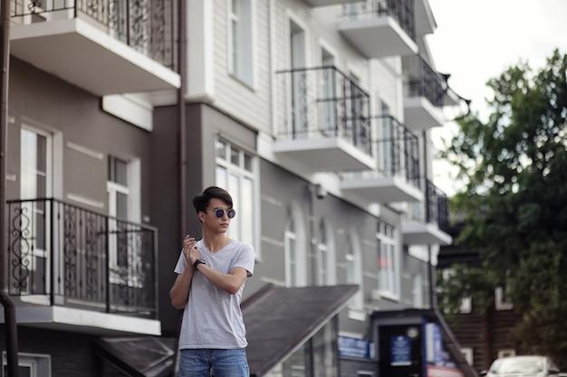도시에서 야외에서 선글라스를 끼고 있는 아시아 청년