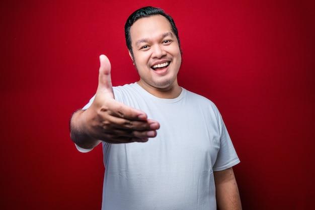 白いtシャツを着たアジアの若い男は、挨拶と赤い背景の上で歓迎として握手を提供するフレンドリーな笑顔をしています。成功したビジネス。