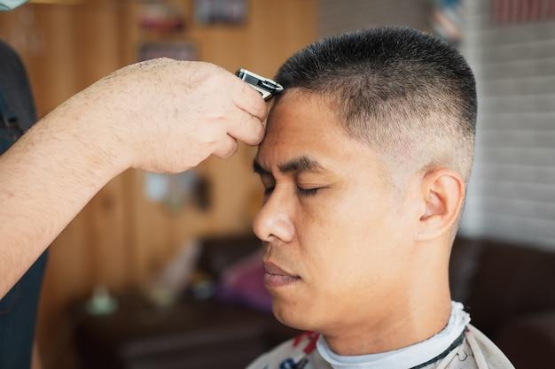 Азиатский молодой человек с седыми волосами, стригущийся на электрической машинке для стрижки профессиональным парикмахером в парикмахерской.
