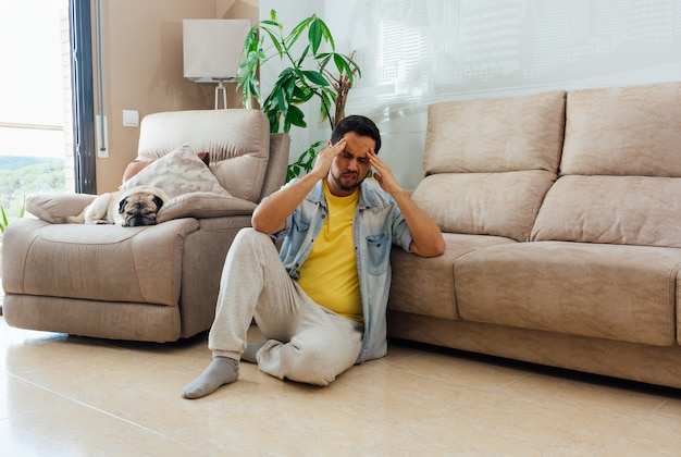 Asian young man with depression sitting on the floor at home