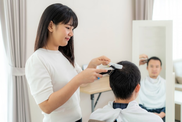 Asian young man with her girlfriend hairdresser cutting hair with an electric hair clipper at home they stay at home during time of home isolation against novel coronavirus or covid-19