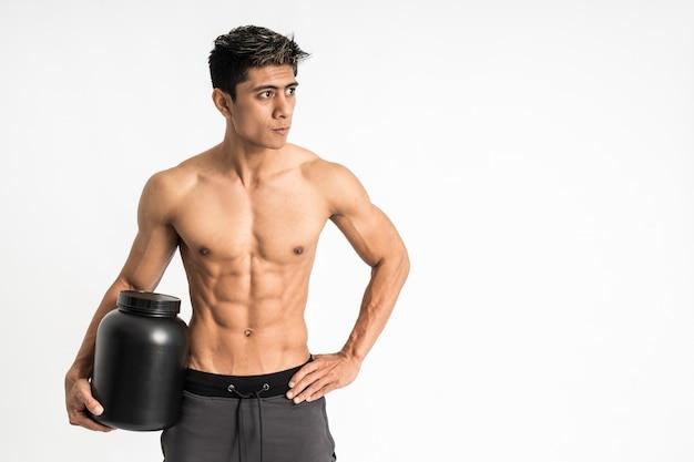 Азиатский молодой человек с мускулистым телом несет черную бутылку с одной рукой, встает лицом вперед и смотрит в сторону