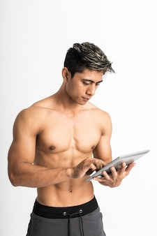 Asian young man with muscular body holding a tablet with two hand typing stand facing forward and look at a tablet
