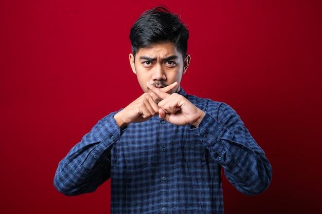 カジュアルなシャツの拒否表現を身に着けている口ひげを持つアジアの若い男は、赤い背景の上に負の記号を行う指を交差させます