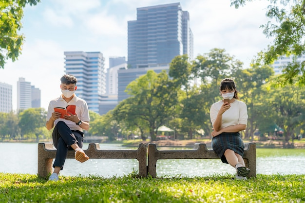 Asian young man and woman reading book and chatting in smartphone and wearing mask sitting distance of 6 feet distance protect from covid-19 viruses for social distancing for infection risk