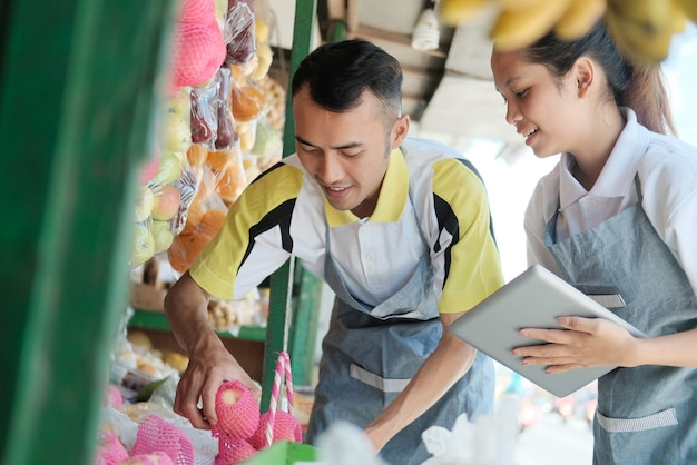 Asian young man and woman worker stands front a display rack fruits while using tablet when prepare