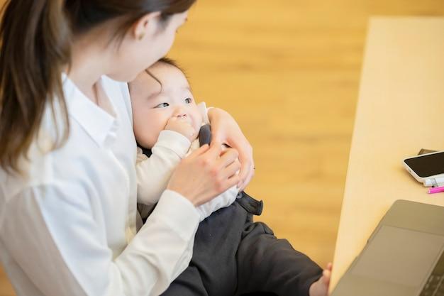 笑顔で赤ちゃんを抱いてアジアの若いお母さん