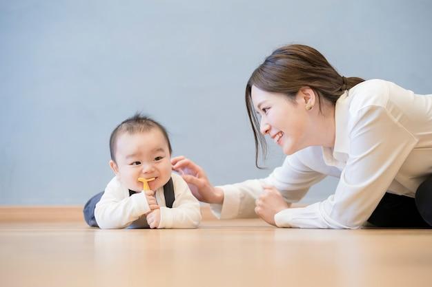 床で赤ちゃんと遊ぶアジアの若いお母さん