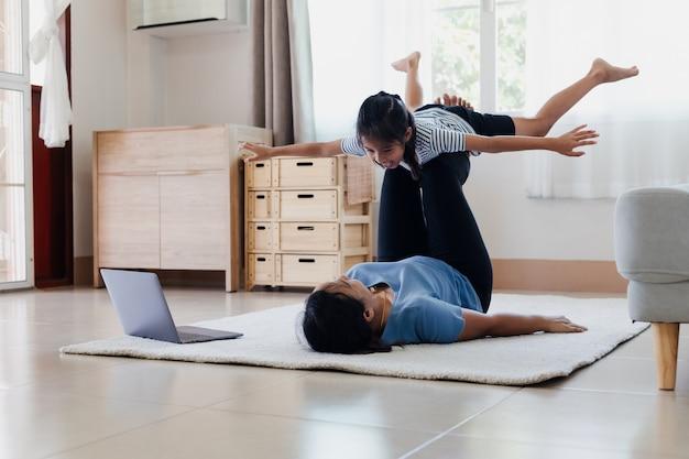 ストレッチフィットネスをしているアジアの若い母と娘は家で一緒にヨガをします。親が子供を教えることは、強くなり、日常生活の中で身体の健康と幸福を維持するように働きます。