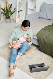 Asian young mother feeding breast her baby during work break while sitting on the floor in front of ...