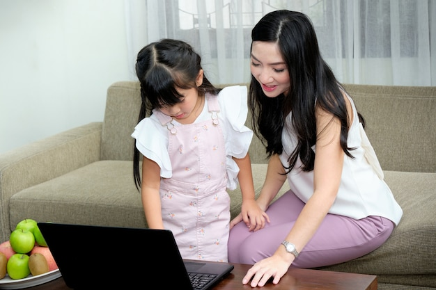Asian young mother sitting on sofa in the living room with her daughter while is teaching the use of laptop