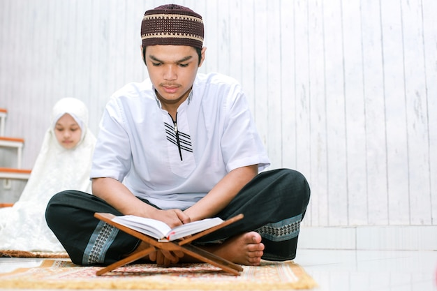Asian young mulim couple sitting and reading holy book alquran together on the prayer mat at home