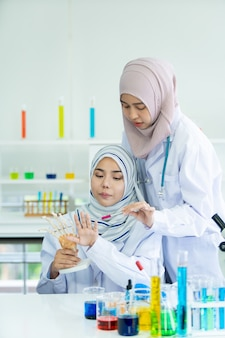 Asian young muslim science student making the experiment in laboratory in their university. muslim scientists investigating a chemical sample. bio technology development in asian countries concept.