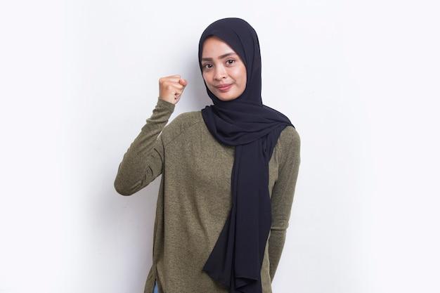 아시아 젊은 이슬람 여성은 흰색으로 큰 성공을 표현하는 승리를 축하하며 행복하고 흥분했습니다.