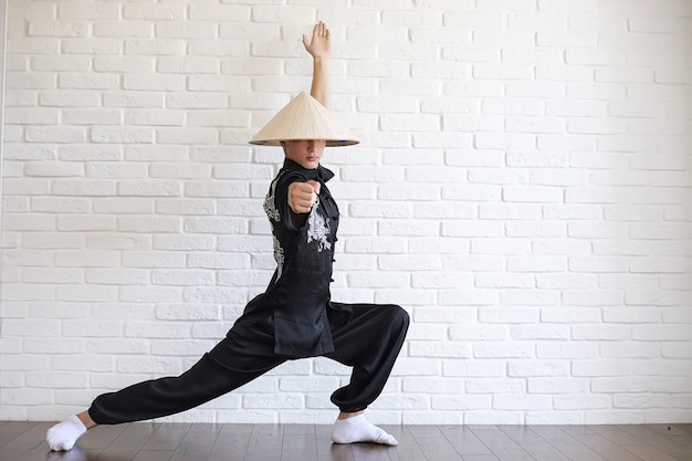 Азиатский молодой послушник на фоне белой кирпичной стены