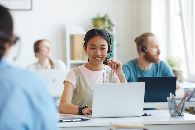 職場に座ってヘッドセットを着用し、同僚とオフィスで働いているラップトップを使用しているアジアの若いオペレーター