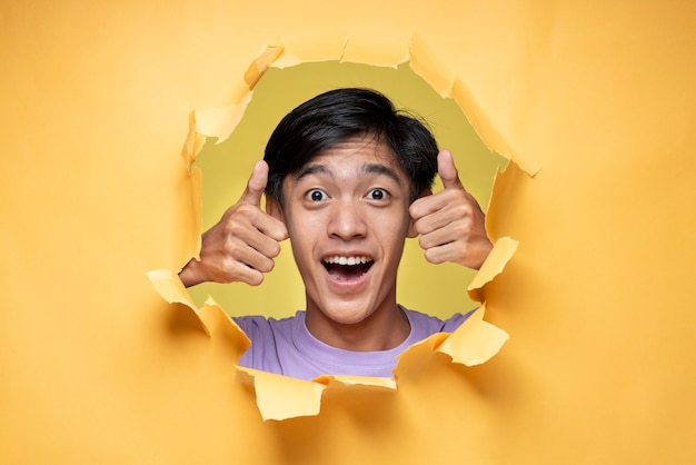 Asian young optimistic man poses through torn yellow paper hole, showing thump up with positive emotions of content and happiness. concept of satisfaction with quality and recommendation
