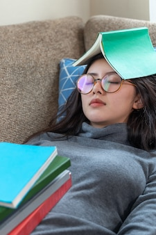 Asian young pretty woman sleeping on couch while stack of books placed on her body