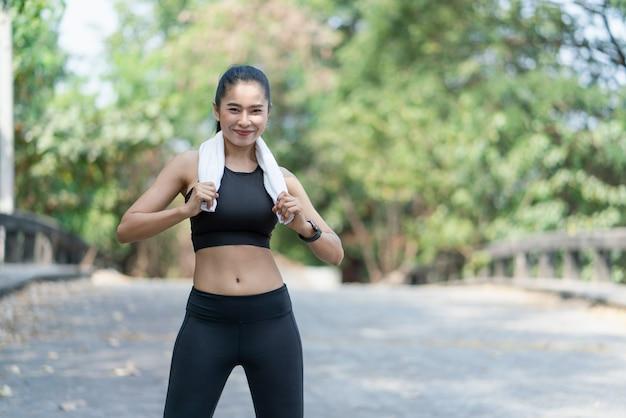 야외에서 운동한 후 카메라를 쳐다보는 하얀 수건을 들고 있는 아시아 젊은 스포츠 여성