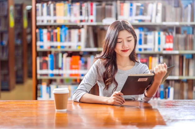 Asian young student in casual suit reading the book with a cup of coffee in library of university or colleage on the wooden table over the book shelf wall, back to school concept