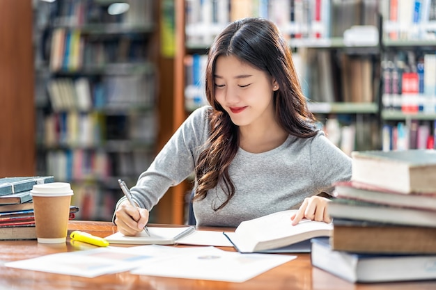 Asian young student in casual suit reading and doing homework in library of university or colleage