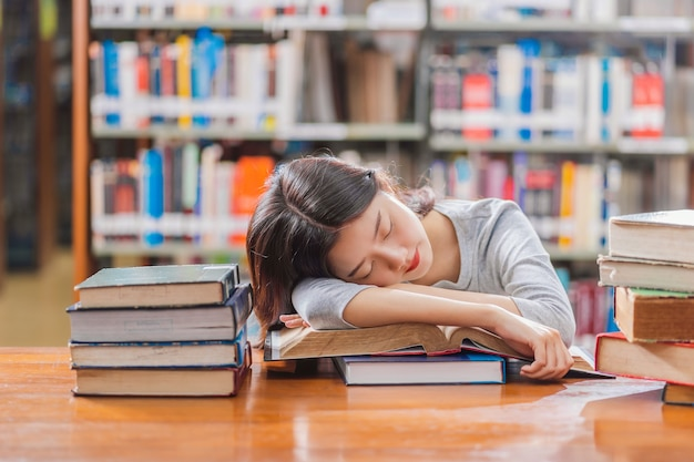 Asian young student in casual suit reading and sleeping on the wooden table with various book