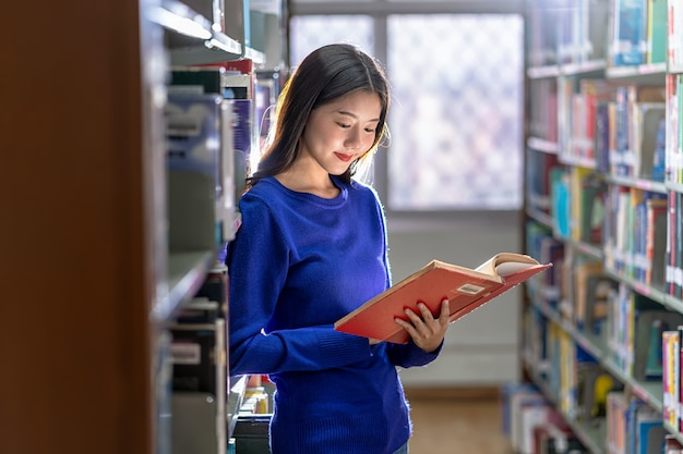 Asian young student in casual suit standing and reading the book at book shelf in library of university or colleage with various book wall, back to school concept
