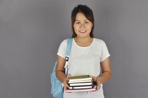 アジアの若い学生のバックパックに笑みを浮かべて、本を保持しています。