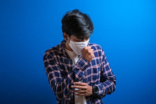 아시아 젊은 학생은 파란색 배경에 대한 얼굴 마스크 보호로 기침을 하고 있다