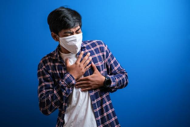 フランネルシャツを着たアジアの若い学生は胸に痛みを感じ、青い背景にコロナウイルスが広がるのを防ぐために保護マスクを着用します