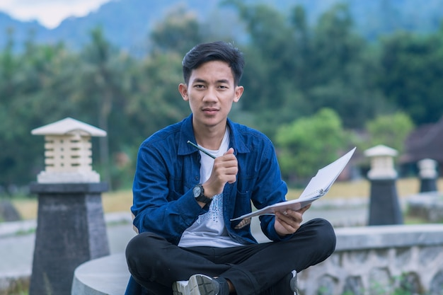 아시아의 젊은 학생들이 앉아서 공원에서 책을 읽고, 책을 열고, 공원에서 공부합니다.