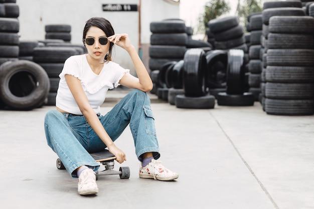 アジアの若い10代、現代の10代の少女、スケートボードまたはサーフボードを持つz世代の流行に敏感な女性