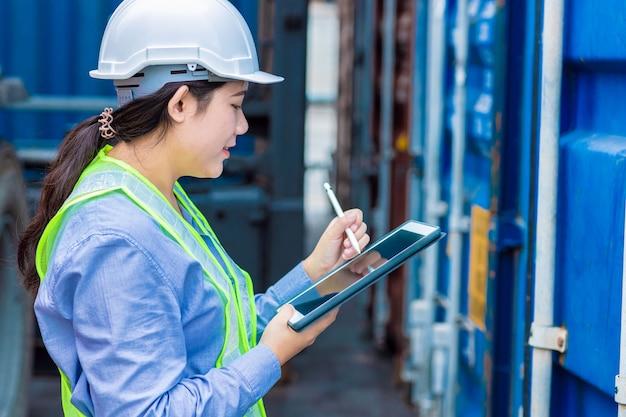 Азиатский молодой подросток, работающий в зоне погрузочной логистики, использует планшетную беспроводную технологию для проверки таможенных деталей кода импортно-экспортного контейнера.