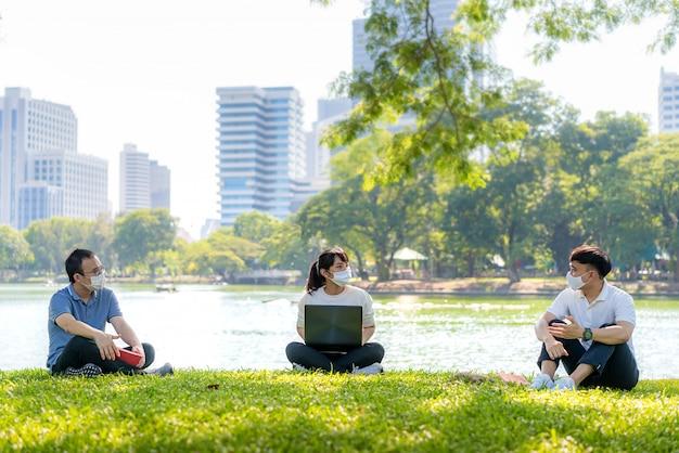 아시아의 젊은 세 남자와 여자 이야기하고 그들과 함께 휴식을 취하고 6 피트 거리의 마스크 앉아 거리를 착용하여 사회적 거리를 위해 covid-19 바이러스로부터 보호하십시오.