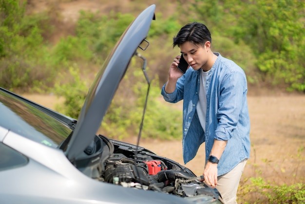 Asian young unhappy man talking on a cell phone  in front of the open hood  broken down car on country road phoning for help.