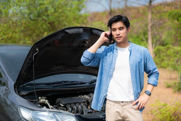 開いたボンネットの前で携帯電話で話しているアジアの若い不幸な男が車を破壊しました。