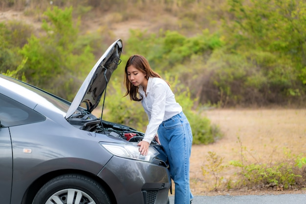 Asian young unhappy woman  inspecting broken car engine  in front of the open hood  broken down car on country road waiting for road assistance service.
