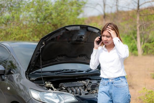開いたボンネットの前で携帯電話で話しているアジアの若い不幸な女性が車で国の道路に電話をかけた。