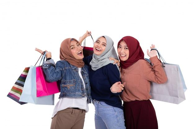 ショッピングの後に紙袋を運ぶアジアの若いベールに包まれた女性