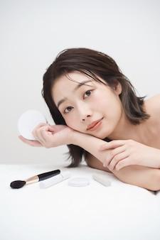 Азиатская молодая женщина и косметические предметы