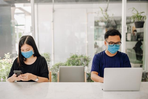 アジアの若い女性とオフィスでマスクを着ている男