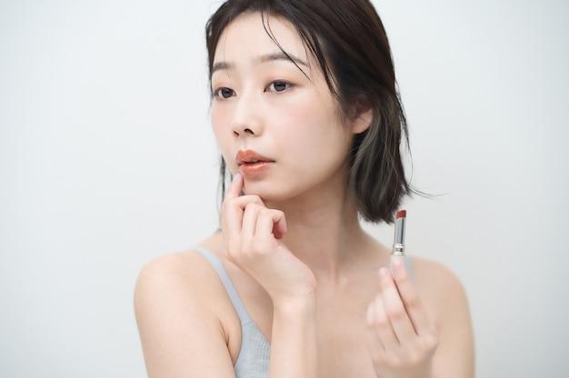 Азиатская молодая женщина, наносящая помаду на губы