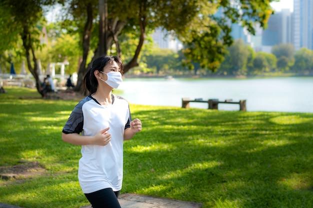 아시아 젊은 여성이 조깅하고 도시 공원에서 야외 소비하고 방콕, 태국에서 covid-19 전염병 동안 맞는 체재를 위해 얼굴에 보호 마스크를 착용하고 있습니다.