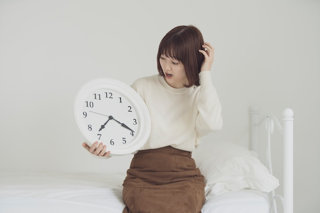 Asian young woman astonished to check the clock and be late in time