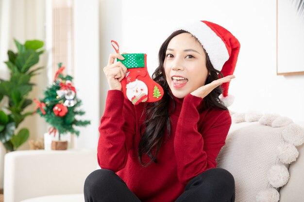 サンタの帽子と靴下とクリスマスの時期に自宅でアジアの若い女性